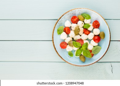 Cherry tomatoes, mozzarella cheese, basil and spices on gray slate stone chalkboard. Italian traditional caprese salad ingredients. Mediterranean food.