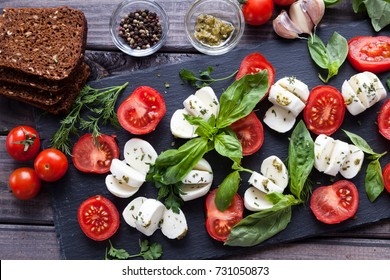 Cherry tomatoes, mozzarella cheese, basil, pesto sauce, dark rye grain bread and spices on black slate stone chalkboard. Italian traditional caprese salad ingredients. Mediterranean food. Top view