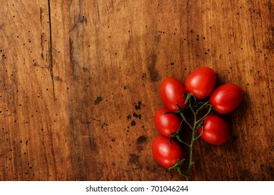 Cherry tomatoes on wooden background. Copy space for design. Top view.