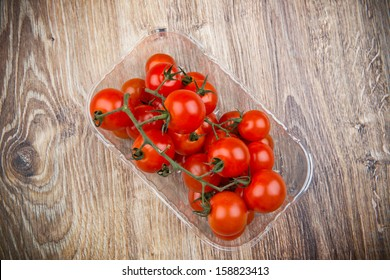 Cherry tomatoes on wooden table in the plastic box