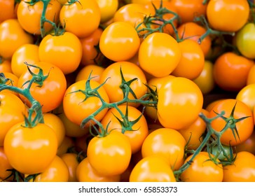 Cherry tomatoes in a pile for sale at a farmers market.
