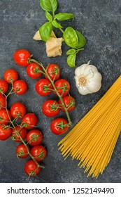 Cherry tomatoes with spaghetti and garnish on dark background. Copy space vertical.