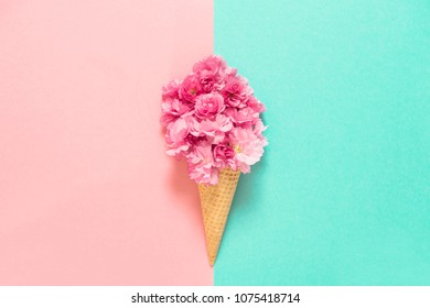 Cherry tree blossom in ice cream waffle cone. Pink flowers on blue background. Styled flat lay. Minimal concept