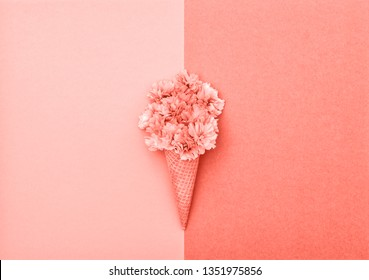Cherry tree blossom in ice cream waffle cone on pink background. Styled flat lay