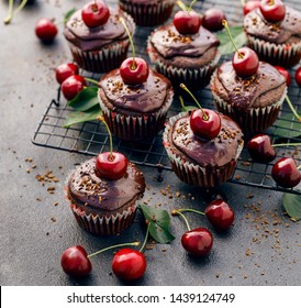 Cherry-Chocolate-coffee muffins with melted dark chocolate topping with the addition of fresh cherries on on a cooling tray, on a dark background, close-up. Delicious dessert