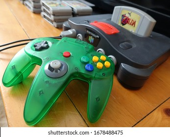 Chertsey, Quebec - 18 March 2020 : Close view of a used Nintendo 64 retro game console with green controller and Zelda Ocarina Of Time game cartridge inserted