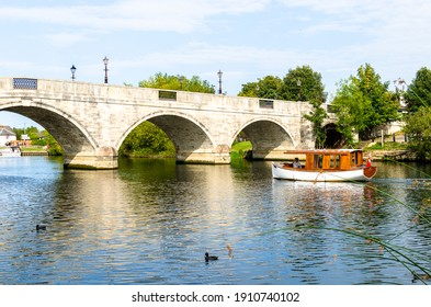 Chertsey, Surrey, England - September 20, 2020: A recreational boat by the Chertsey Bridge on the River Thames in summer