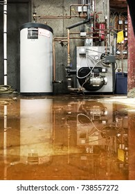 CHESHIRE, CT, USA - OCTOBER 2017: A burst pipe at the furnace and water tank has caused a leak on the basement floor of a house.