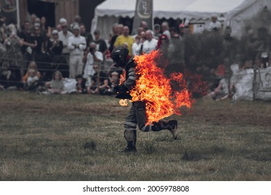 Cheshire, UK - 10th July 2021: A stunt man runs in front of crowd on fire. Cheshire Steam Fair