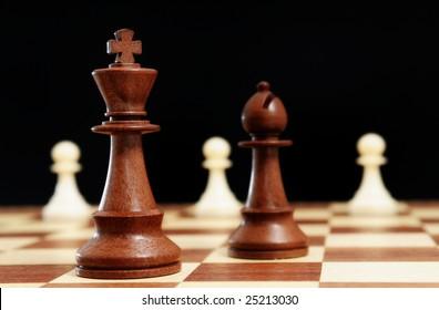 Chess - Black King, black bishop and white pawns on black background