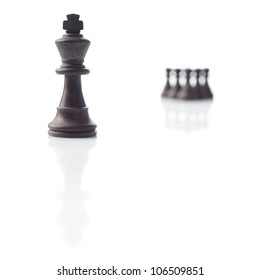Chess. Black king, five pawns out of focus and their shadows on white background