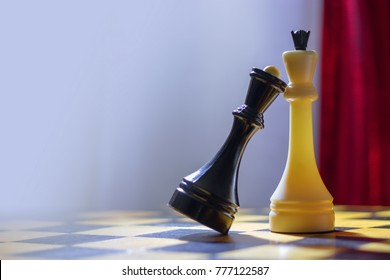 Chess black queen and white king stand on a wooden chessboard. The black queen put her head on the chest to the white king.