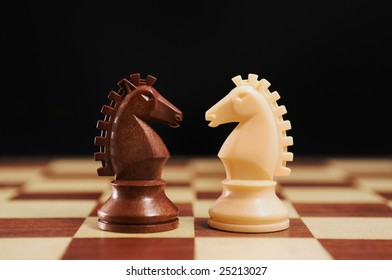 Chess - black and white horses on a chessboard and black background