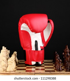 Chess board and boxing glove isolated on black
