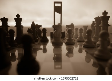 Chess board game concept of business ideas and competition and strategy ideas. Chess figures and Guillotine on a chessboard. Outdoor misty dark background. Selective focus