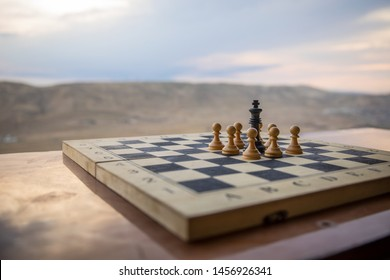 Chess board game concept of business ideas and competition. Chess figures on a chessboard. Outdoor sunset background. Selective focus