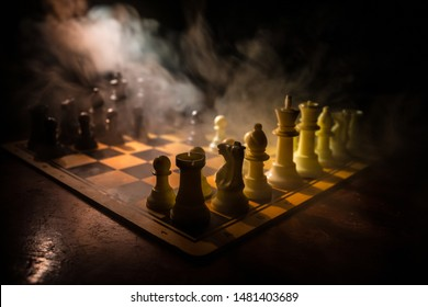 Chess board game concept of business ideas and competition. Chess figures on a dark background with smoke and fog. Selective focus