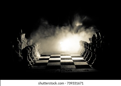 Chess board game concept of business ideas and competition and strategy ideas concep. Chess figures on a dark background with smoke and fog. Selective focus