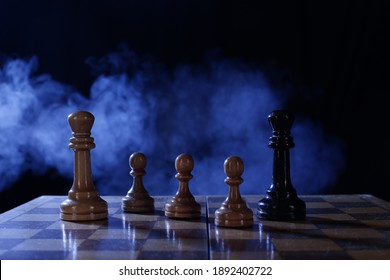 Chess is a board game. Chess pieces on a dark background in smoke