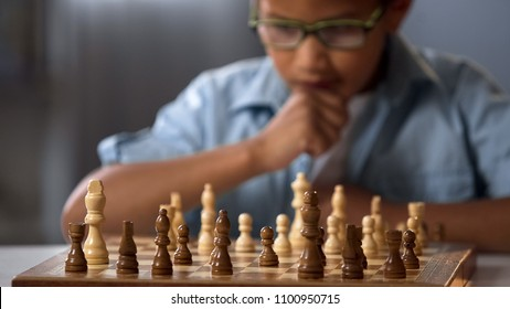 Chess board on table in front of school boy thinking of next move, tournament