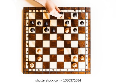 Chess board on white background. Little caucasian girl holding a black castle in the hand. The chess game. Top view.