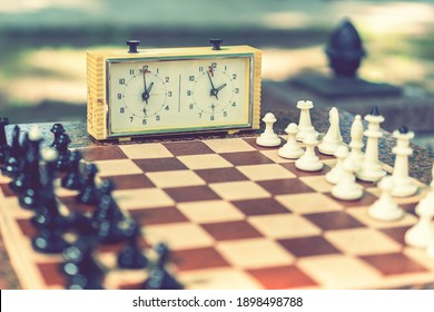 Chess board with pieces and clock on wooden desk In connection with the chess tournament. Chess pieces and stopwatch on a board in the park. toned.