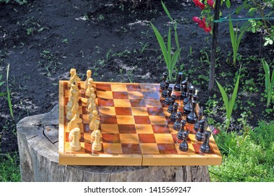 Chess board with chess pieces on an old stump in a country house.