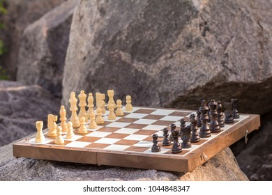 Chess Board With Chess Pieces On Stone With Big Rocks On The Background.  Outdoors Chess