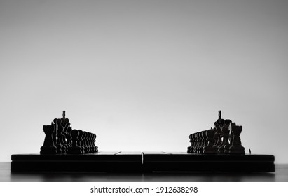 Chess board with chess pieces silhuettes on white background. Concept of business ideas, competition and strategy ideas. Black and White classic art photo. All figure ready for battle, before opening