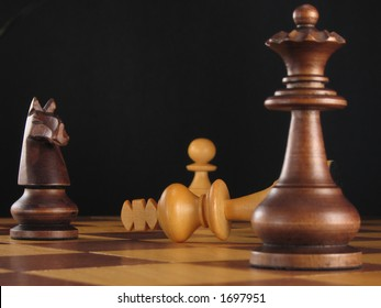 Chess board still life of a triumphant queen and knight standing over a defeated king and pawn against a black background.