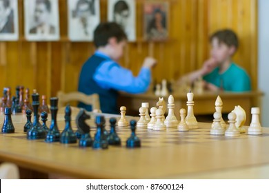 Chess board with two players blurred on the background