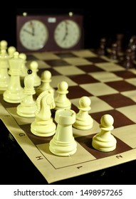 Chess board with white figures in focus and clock in the background.