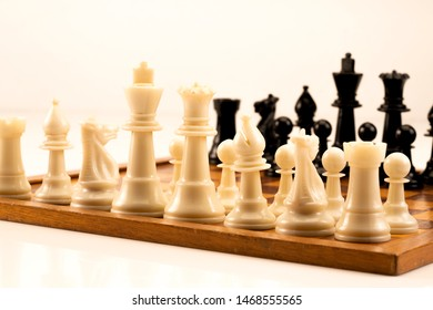Chess board with chess wooden pieces isolated on white, focussed on the white queen.