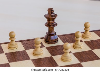 chess game. abstract composition of chess figures in chessboard isolated on light background. black king surrounded white pawns.
