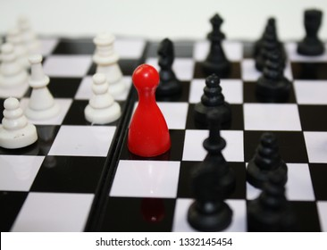 Chess game with bright red ludo piece in the middle of the game.
