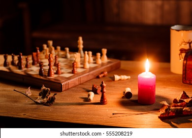 Chess game with the candle on grunge wooden table black background. Atmospheric view with warm light. Still life in the rustic house.
