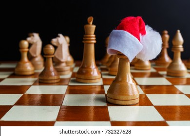Chess game with figures in a Christmas cap on a wooden brown field, the concept of a tournament, the sport of family festive New Year's games with a copy of space and a selective focus