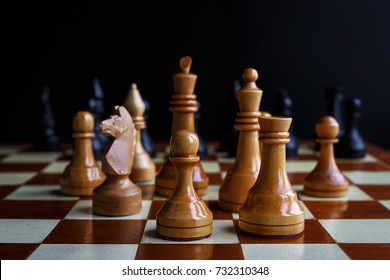 Chess game with figures on a wooden brown field, the concept of a tournament, a sport with a copy space and a selective focus