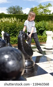 Chess game with giant chess piece. child playing strategic outdoor game on black and white board