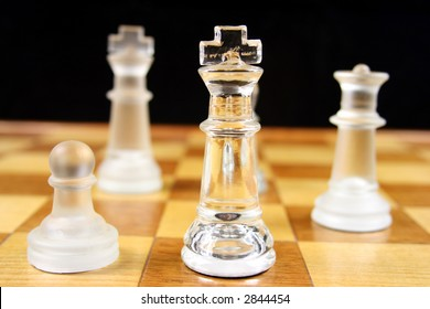 Chess Game - Glass Chess Pieces on a wooden chessboard