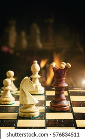 Chess game on the background of a burning fireplace. See series