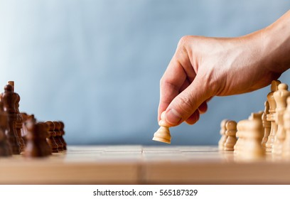 Chess game player makes a move the white pawn one step forward. Chess pieces on the board on blue background. Chessman playing chess, and showing the hand.