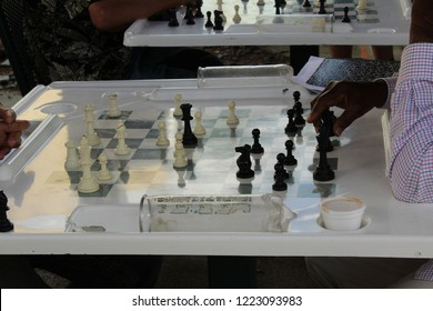 Chess game in progress on white table shows black man's hands and arms. In background is another chess game in progress.