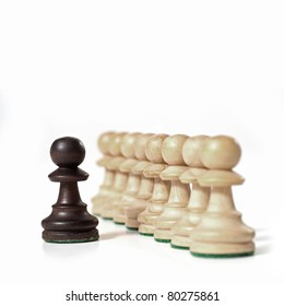 Chess game. White prawns in a row with black one. Leadership concept.