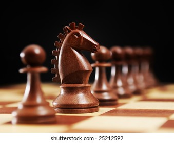 Chess - horse and black pawns on a chessboard and black background