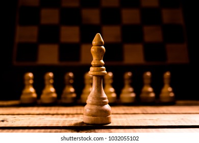 chess king in focus and pawns on blurred background