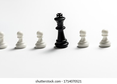 chess king is standing against white pawns. Symbol of leadership and confrontation.