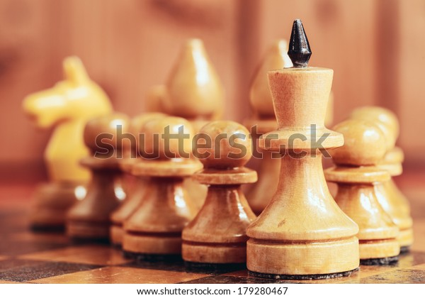 Chess leader led king his army white wooden figures. Concept game. Close up focus