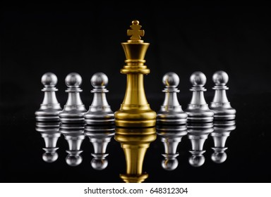Chess leadership concept with gold and silver chess isolated in black background