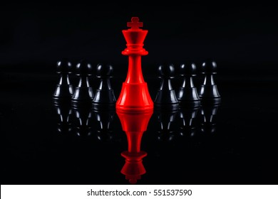 Chess leadership concept with red and black chess isolated in black background